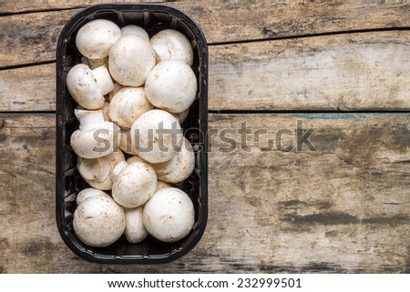 Fresh raw mushrooms in plastic container on wooden background with copy space - stock photo