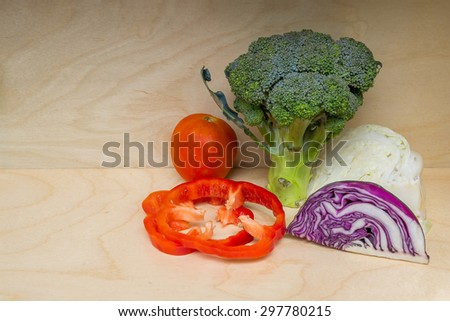Fresh raw organic vegetable produce, peppers, broccoli,cabbage,tomatoes, isolated on wood background - stock photo