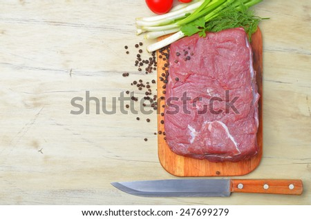 Fresh raw piece of meat lies on the kitchen blackboard next to onions, parsley and tomatoes and a knife with a wooden handle on a wooden table, top view - stock photo