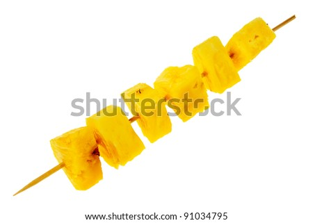 Fresh, raw pineapple chunks nailed on wooden stick isolated over white background. - stock photo