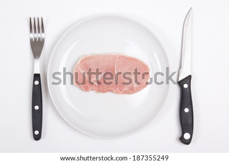 fresh raw pork chop on a white plate with fork and knife - stock photo