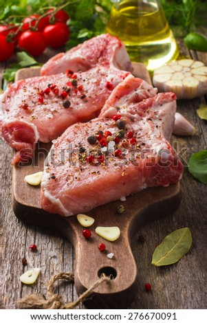 Fresh raw pork chops with spices and herbs on wooden background - stock photo