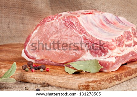 fresh raw  pork loin with bay leaf on wooden board and on the background of sacking - stock photo