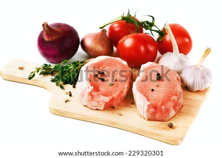 Fresh raw pork meat steaks served with tomato, onion, garlic and fresh herbs over white background - stock photo