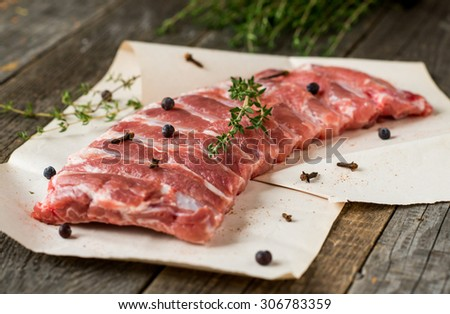 fresh raw pork ribs with herbs on vintage background - stock photo
