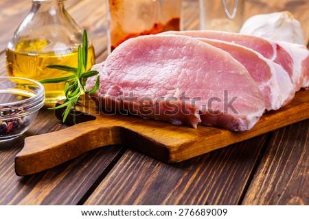 Fresh raw pork slices on a chopping board - stock photo