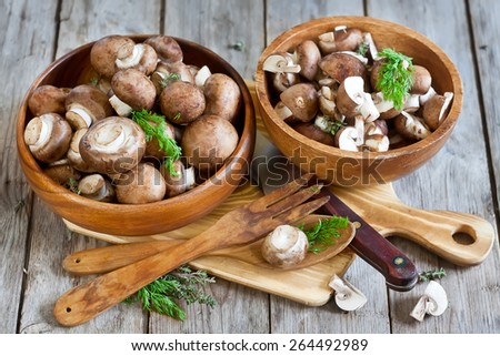 Fresh raw portabello mushrooms with knife in wooden bowls on old wood background - stock photo