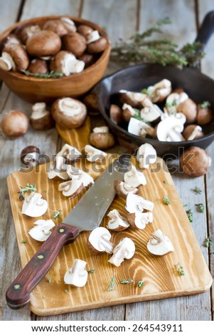 Fresh raw portabello mushrooms with knife on chopping desk on old wood background. Selective focus. - stock photo