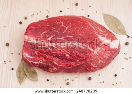 Fresh raw red beef meat on wooden table - stock photo