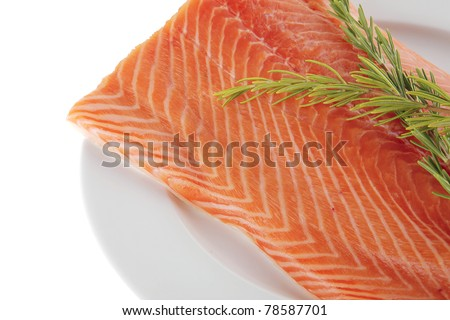 fresh raw red fish fillet on white plate and rosemary