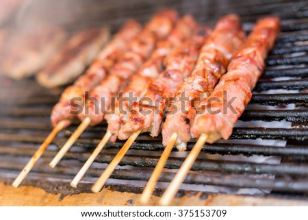 fresh raw red meat pork breast fillets on a skewer barbecue grill grid roasts.skewers of pork on a wooden stick. Greece, souvlaki. - stock photo