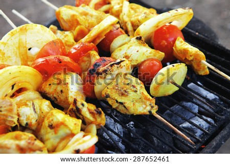 fresh raw roast shish kebab on barbecue grill grid coocked over hot charcoal - stock photo