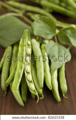Fresh raw runner beans on wooden background - stock photo