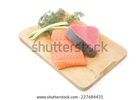 fresh raw salmon and red tuna fish pieces over wooden board isolated on white background - stock photo