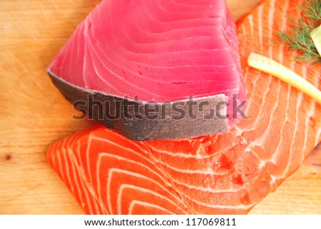 fresh raw salmon and tuna fish  pieces on wooden plate isolated on white background . shallow dof