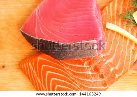 fresh raw salmon and tuna fish  pieces on wooden plate isolated on white background . shallow dof - stock photo