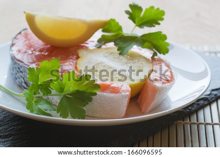 Fresh raw salmon cutlet with lemons and parsley garnish