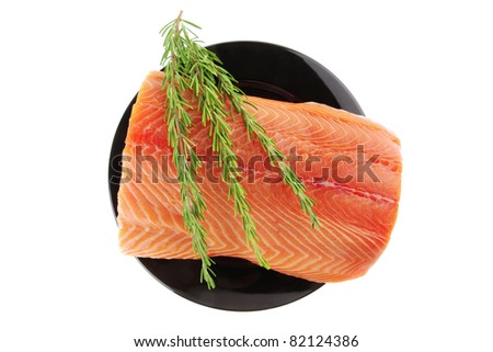 fresh raw salmon fillet on black over white and rosemary