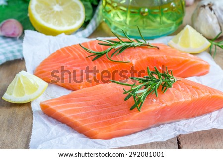 Fresh raw salmon fillet with rosemary and lemon - stock photo