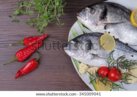 Fresh raw sea bream fish  decorated with lemon and herbs on blue wooden background. Healthy food concept - stock photo