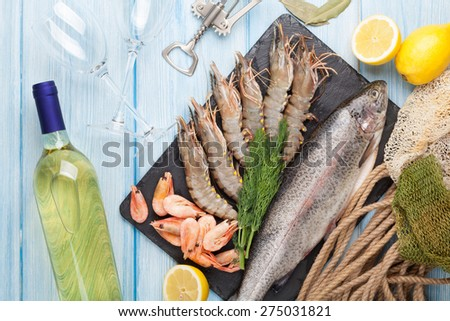Fresh raw sea food with spices and white wine bottle on wooden table background. Top view  - stock photo