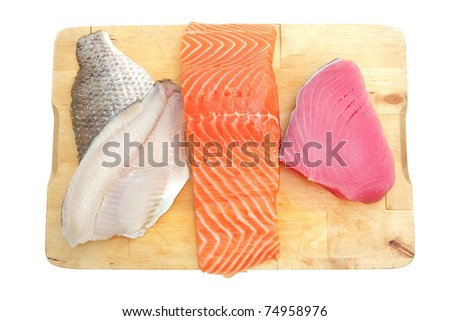 fresh raw sole , salmon , and red tuna fish  pieces on wooden plate isolated on white background - stock photo