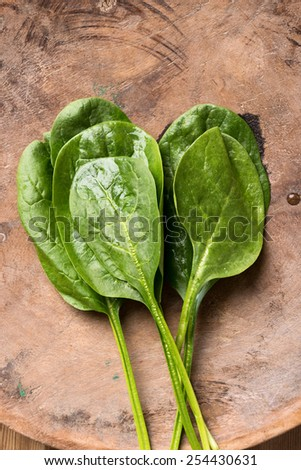 Fresh raw spinach is a rustic wooden bowl set on wood table - stock photo