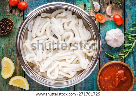 fresh raw squid rings in a steel bowl on a wooden table with tomatoes, lemon, rosemary, garlic - stock photo