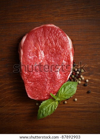 fresh raw steak with pepper and basil on the wooden board. - stock photo