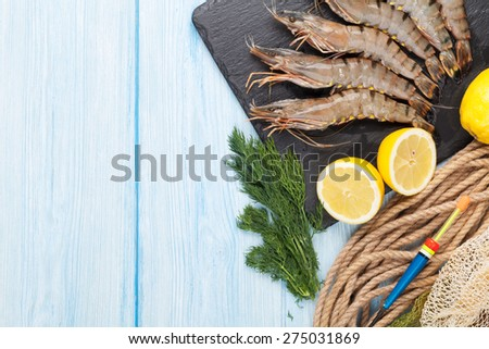 Fresh raw tiger prawns and fishing equipment on wooden table. Top view with copy space  - stock photo