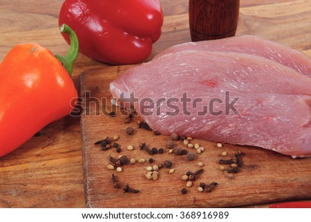 fresh raw turkey meat steak with hot sweet pepper dry spices castor and pepperbox on wood cutting boar over table - stock photo