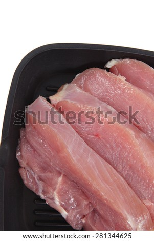 fresh raw turkey pieces on black pan isolated over white background