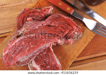 fresh raw uncooked beef fillet mignon entrecote on board prepared for cooking on wood table with cutlery and castors - stock photo