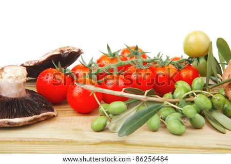 fresh raw vegetables on wooden board over white - stock photo