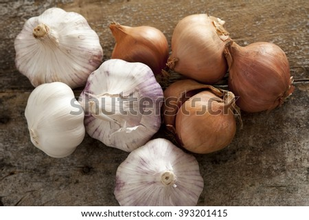 Fresh raw whole garlic bulbs and brown onions, both of the Allium family, on a rustic wooden table viewed from overhead - stock photo