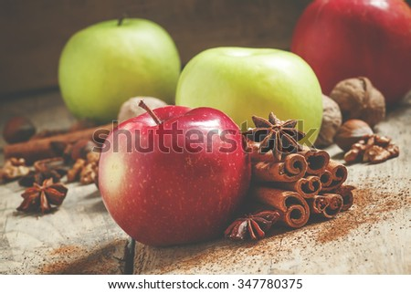 Fresh red and green apples, cinnamon sticks, ground cinnamon, anise stars, walnuts and hazelnuts on an old wooden background, selective focus