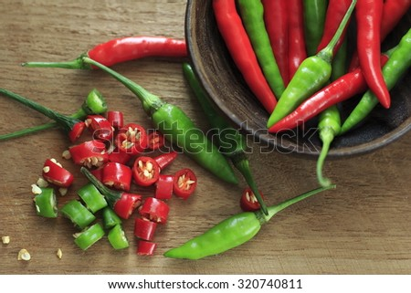fresh red and green chilli and chopped fresh red and green chilli on wooden chopping block. guinea pepper ;bird pepper ; bird-chilli ; small capsicum ; chilli pepper ; tiny fiery chilli ; hot chilli .