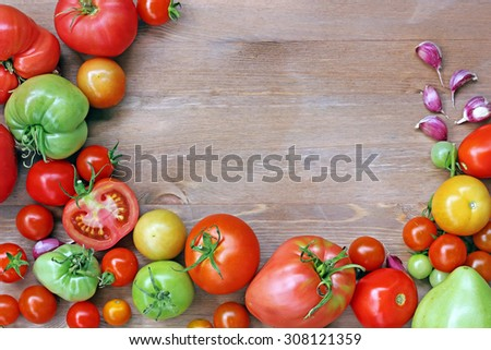 Fresh red and green tomatoes and garlic on a table, in the center a blank space for your text, the top view. Tomatoes mature and unripe. - stock photo