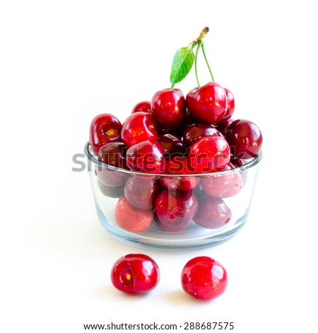 Fresh red and Rainier cherries with leaves on a glass bowl isolated on white background. They are fresh picked in Yakima Valley, a prime agricultural area of Washington State, US.