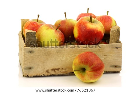 fresh red and yellow apples in a wooden box on a white background - stock photo