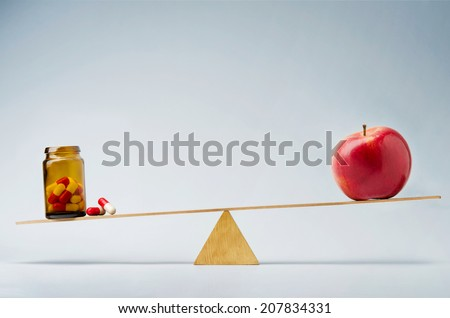Fresh red apple balancing on seesaw over a bottle of pills - stock photo