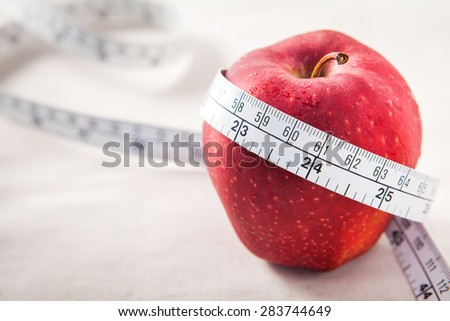 Fresh red apple core and measuring tape. Diet concept - stock photo