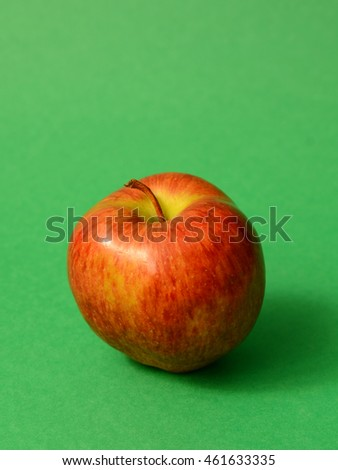 Fresh red apple on a green background