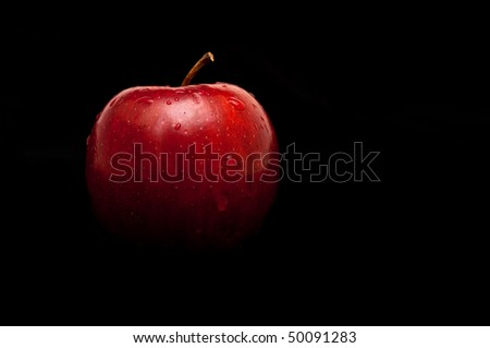 fresh red apple with droplets of water against black background - stock photo
