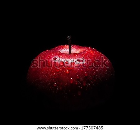fresh red apple with droplets of water against black background with space for text - stock photo