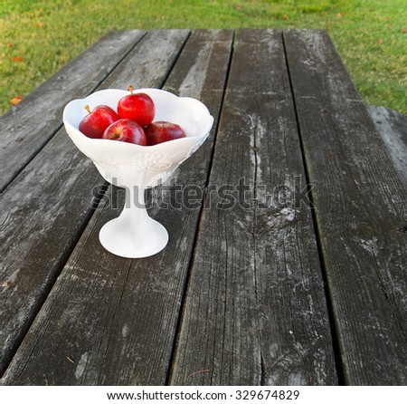 Fresh red apples in a vintage milk glass compote on a picnic table. - stock photo