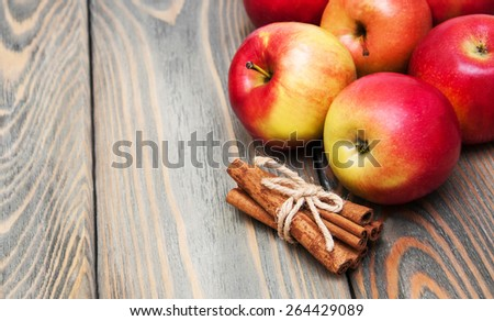 fresh red apples with cinnamon on a old wooden background - stock photo