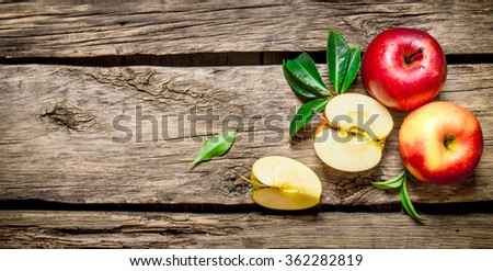 Fresh red apples with green leaves on wooden table. On wooden background. Free space for text . Top view - stock photo