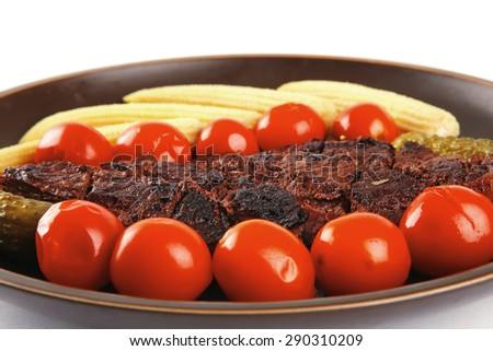 fresh red beef meat served with baby corns and cherry tomatoes on dark plate isolated on white background - stock photo