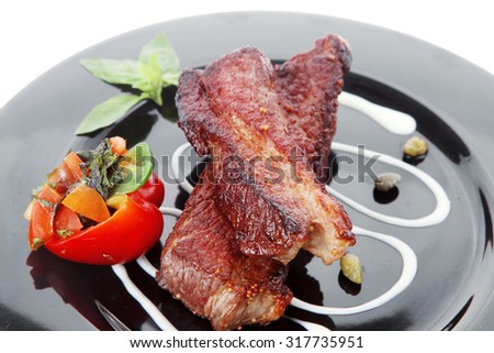 fresh red beef meat steak barbecue garnished vegetable salad sweet potato and basil on black plate isolated over white background - stock photo